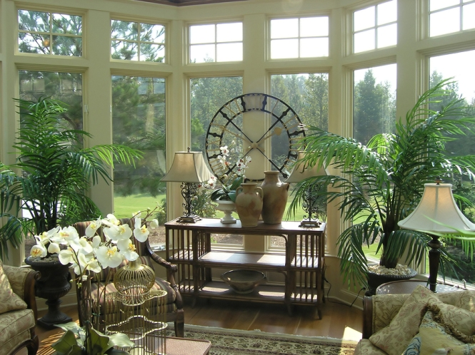 Sun room with towering windows, wood floor, potted palms, rattan furnishings and and large contemporary circular clock overlooks treed grounds