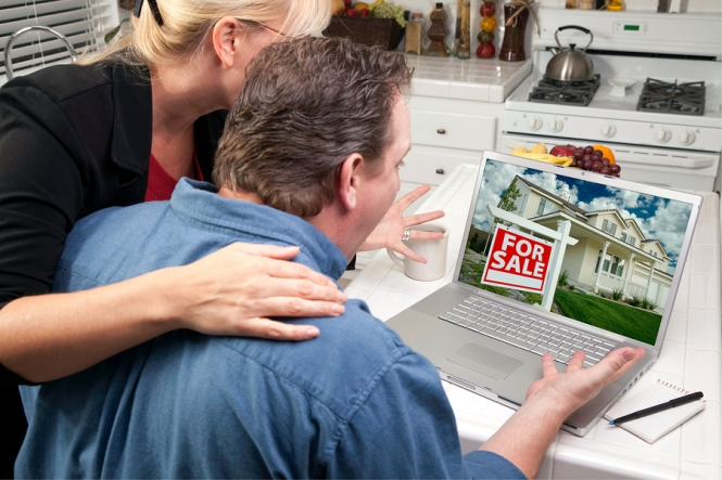 Couple in kitchen looking at a laptop. Close up of laptop screen shows house with For Sale sign in front