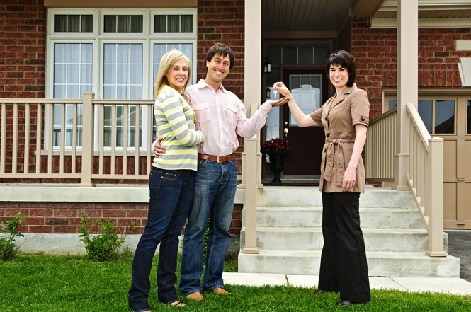 Happy couple in front of porch getting keys to new house from female real estate agent