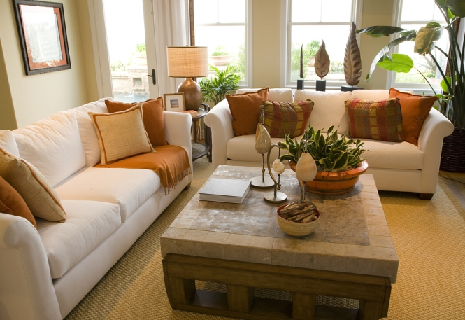 contemporary sofa and coffee table setting in living room with large windows, neutral decor