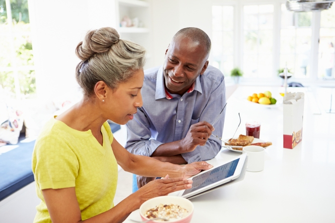 Mature African American Couple Using Digital Tablet At Home at home in the kitchen